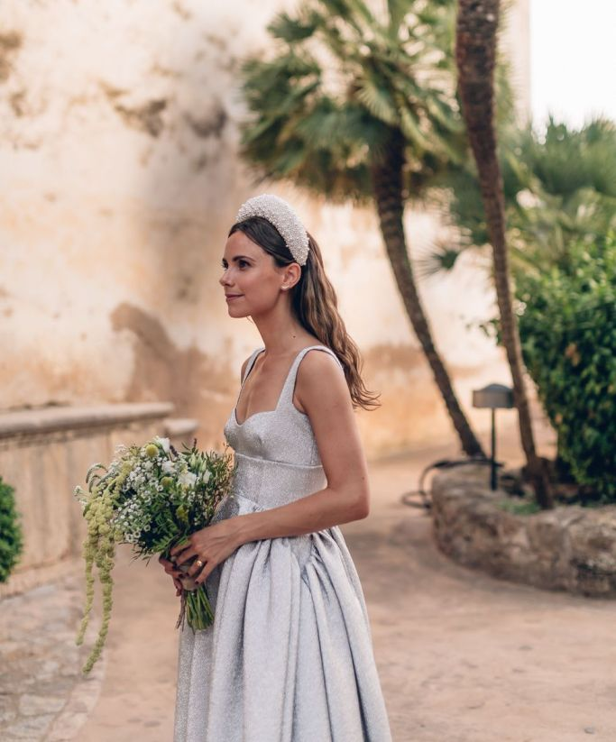 a shiny grey A-line wedding dress on straps plus an oversized stuffed pearl headband and matching earrings for a vogue bridal look