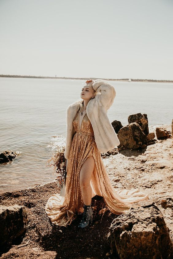 a gold sequin A line wedding dress, black boots, a neutral faux fur coat for a statement and edgy bridal look