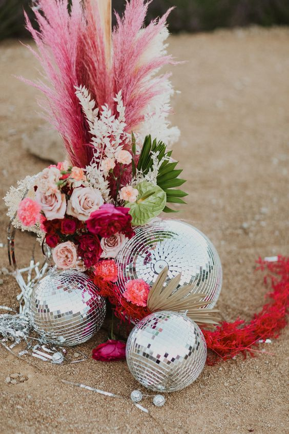 a super bold wedding arrangement of blush and bold blooms, pampas grass, greenery and disco balls by it looks wow