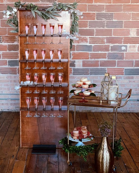 a copper stand with greenery and blooms and drinks in glasses is a very glam and chic idea
