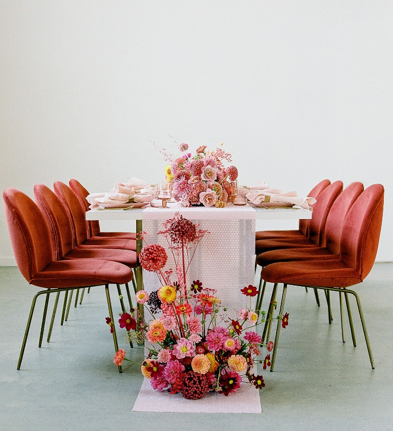 The wedding tablescape was done with pink and mustard blooms and a bold floral arrangement at the table