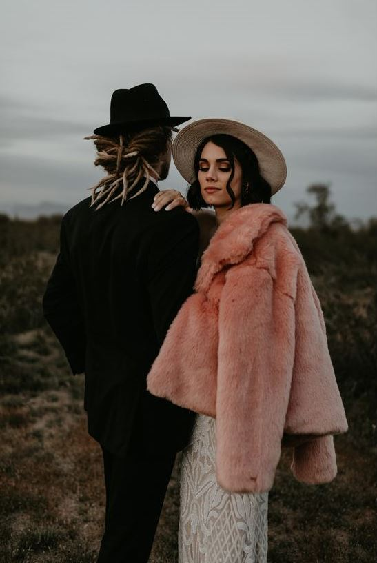 a gorgeous pink faux fur coat over a romantic boho lace wedding dress plus a hat for a boho bridal look