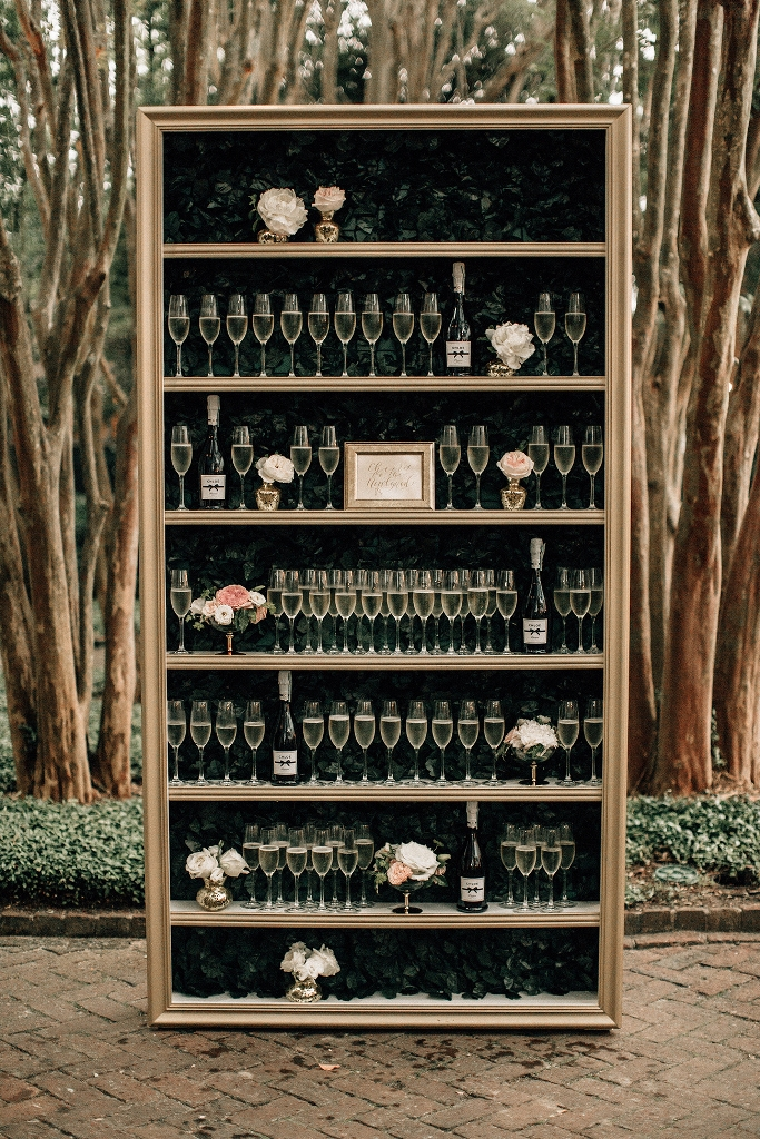 a storage unit with foliage as backing, fresh blooms and drinks on every shelf is very refined