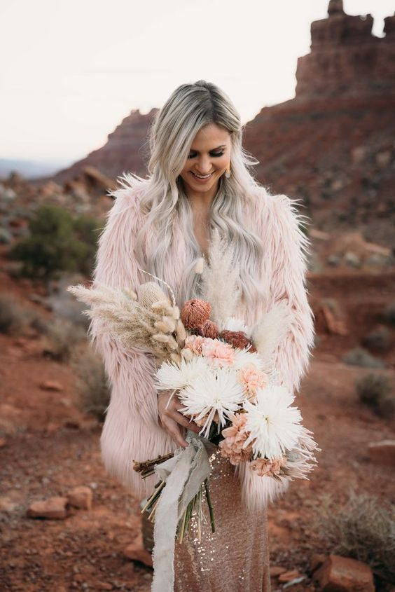 a light pink fuzzy fur coat over a rose gold sequin sheath wedding dress for a bold and edgy boho wedding look