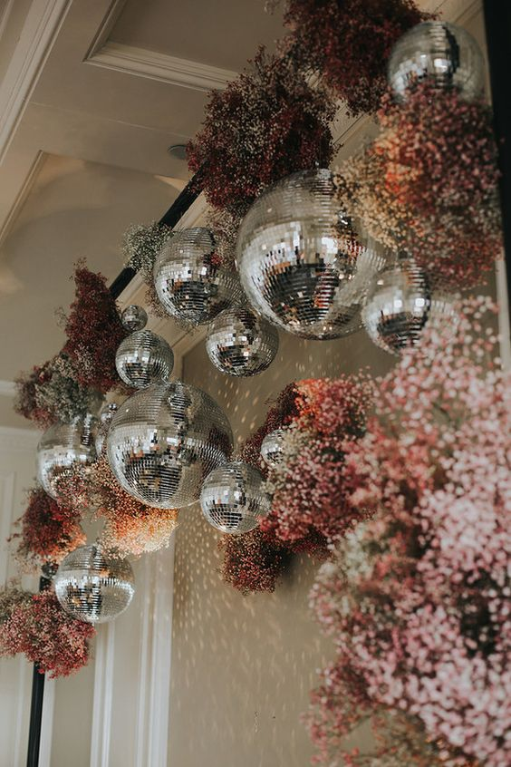 a wedding arch decorated with spary painted baby's breath and disco balls hanging on it looks bright and party-inspired