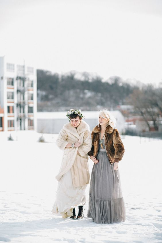 a long neutral faux fur coat over a wedding dress, black boots for feeling comfortable at a wedding outdoors