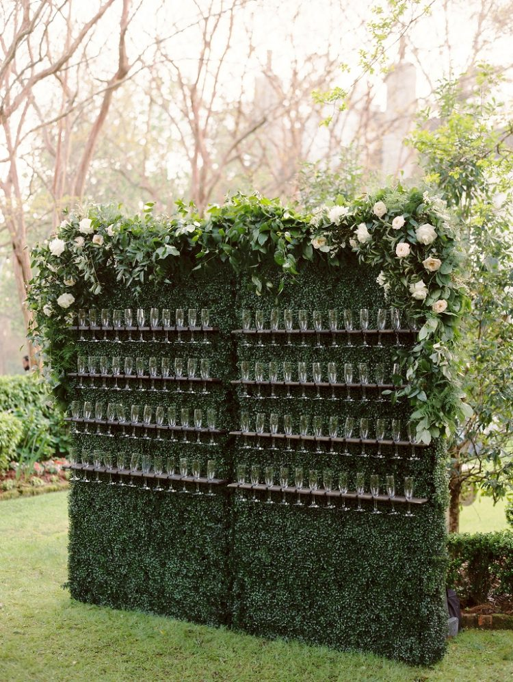 a stunning greenery drink wall with foliage and lush blooms on top is a chic idea to rock