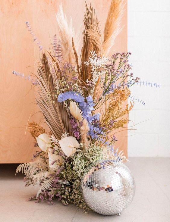 a wedding decor arrangement of pastel blooms, dried herbs and leaves, pampas grass and a disco ball