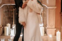 14 a minimalist wedding dress paired with a white faux fur coat with colorful and contrasting embroidery and beading