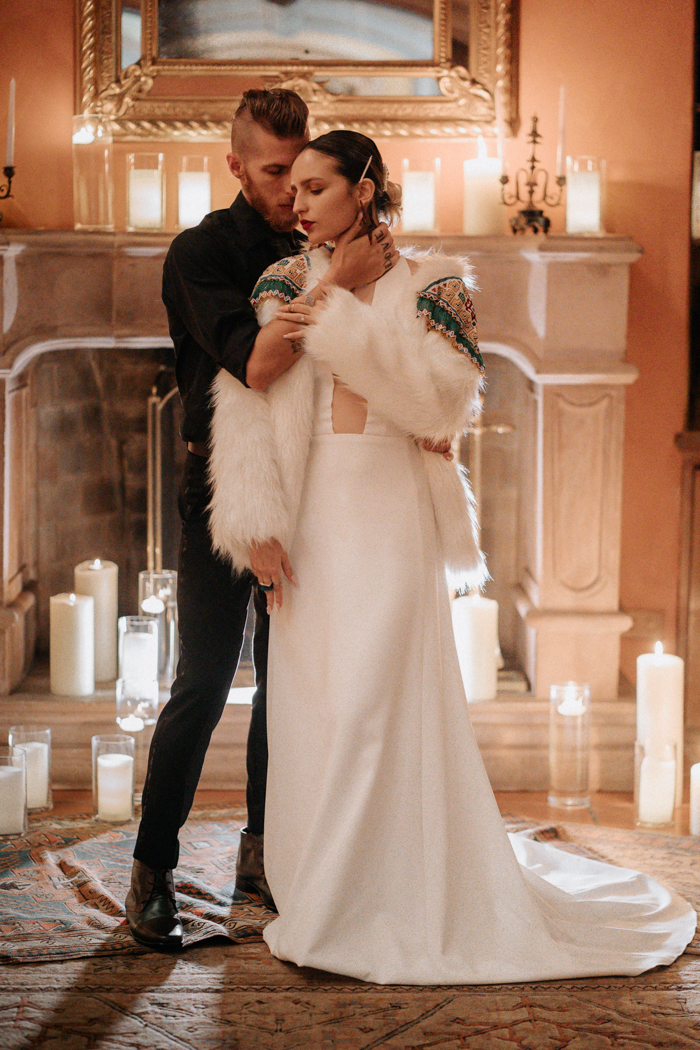 a minimalist wedding dress paired with a white faux fur coat with colorful and contrasting embroidery and beading