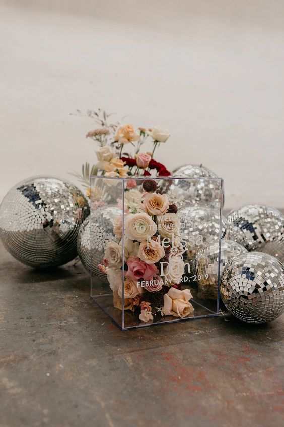 an acrylic cube filled with blooms instead of a sign and lots of disco balls for bold and cool wedding decor