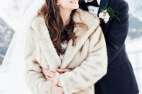 15 a neutral faux fur coat over a wedding ballgown plus a veil for a classic and very romantic bridal look