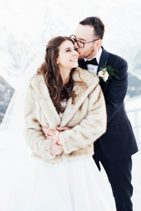 a neutral faux fur coat over a wedding ballgown plus a veil for a classic and very romantic bridal look