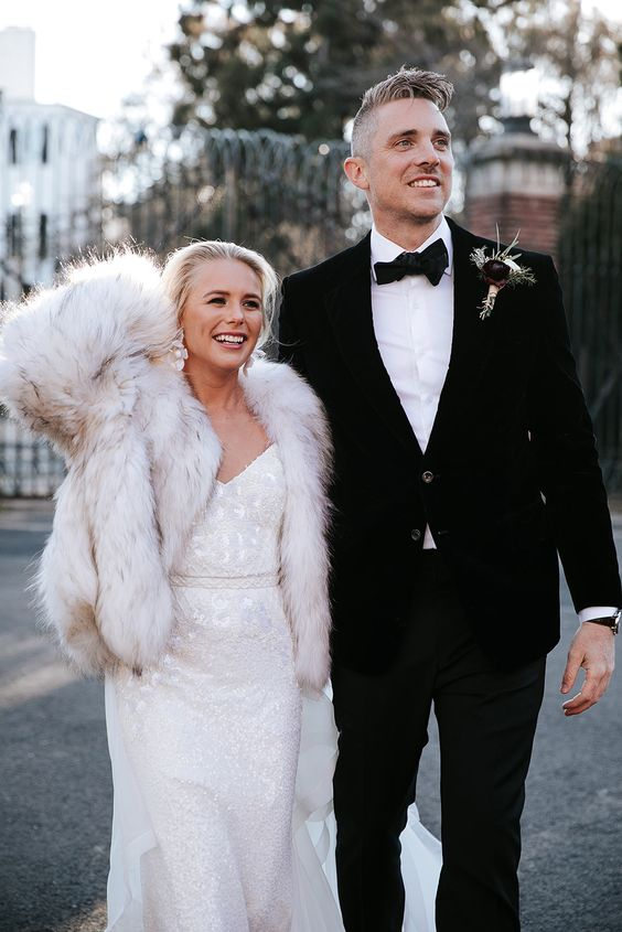a white embellished lace wedding dress paired with a neutral faux fur coat and statement earrings for a glam and luxurious look