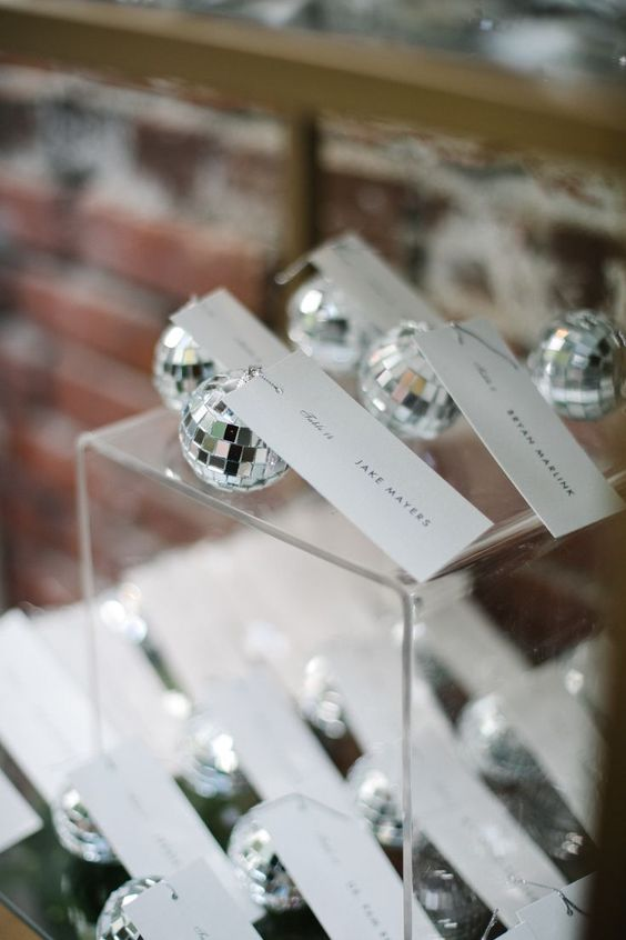 mini disco balls as wedding favors and as place card holders at the same time for a party-themed or a NYE wedding