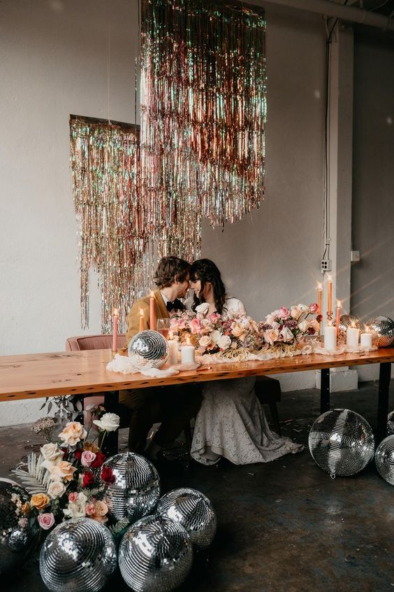 place some disco balls at the table and hang some shiny fringe over it to make it look glam, bold and fun