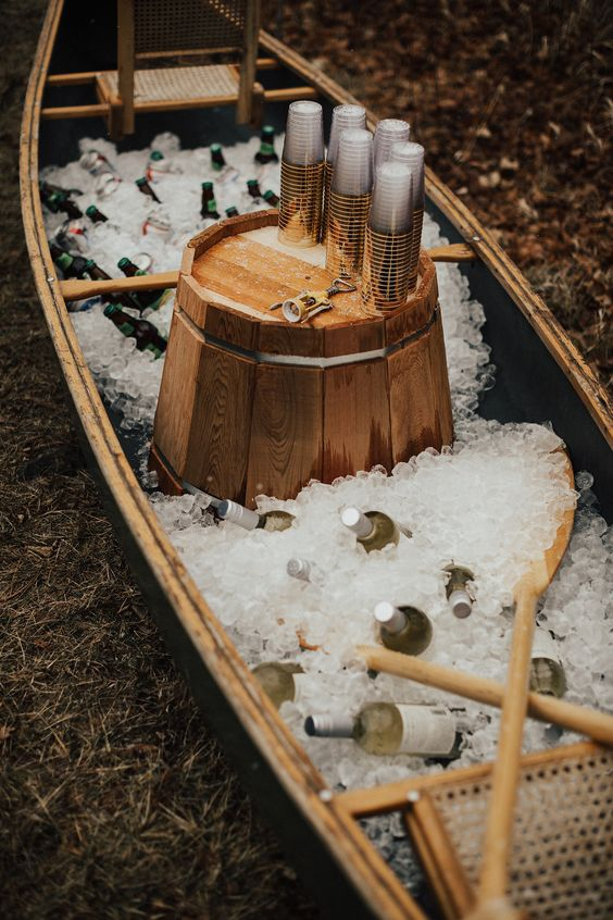 a canoe self-service bar with ice, oars, a wooden bucket and plastic cups