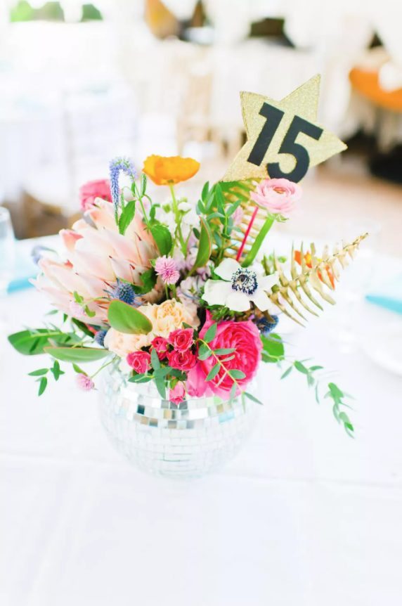 a bold wedding centerpiece of a disco ball as a vase, greenery, bright blooms and a gold sparkle table number