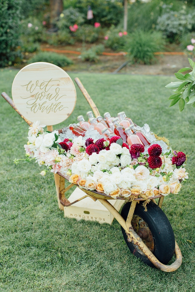 a cart with lots of fresh blooms and leaves and fresh drinks in bottles plus a wooden sign