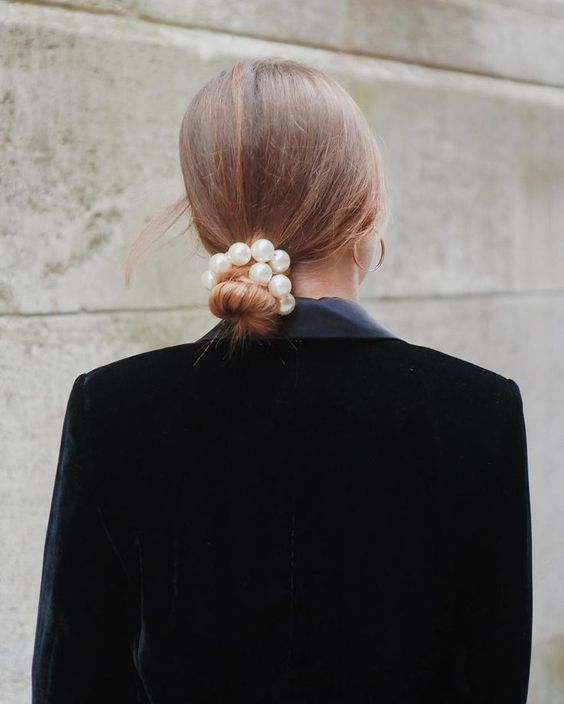 a simple low bun accented with a large pearl hair tie for a modern or very casual bride