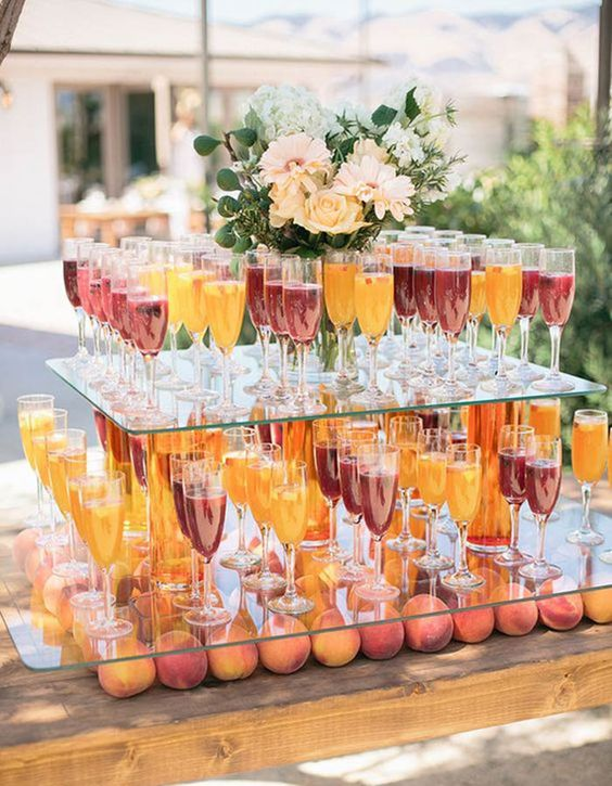 a chic modern stand for drinks with peaches underneath and glass shelves with drinks and flowers