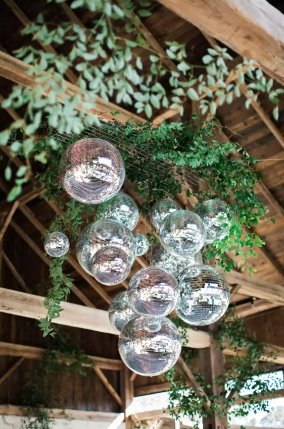 a modern wedding chandelier of greenery on a grid and some disco balls hanging down looks super cool