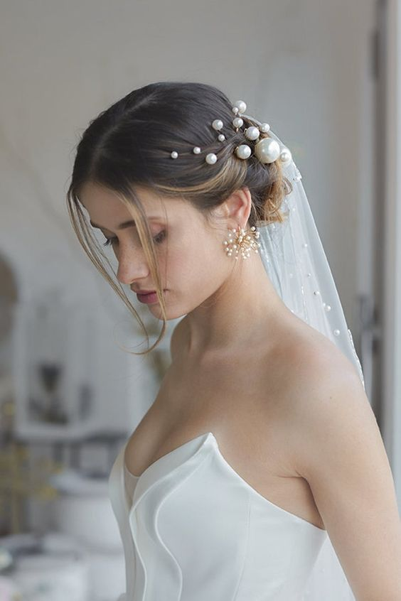 a stylish updo with waves and some locks down, pearl pins of various sizes and a pearl embellished veil, statement pearl earrings