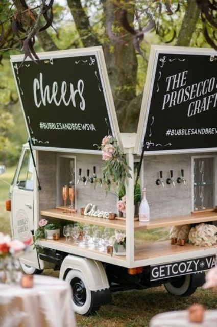 a cool car bar with chalkboards, blooms and greenery, usual and copper glasses is adorable