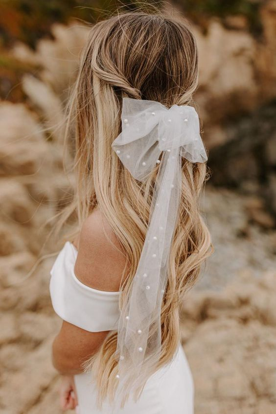 a wavy half updo with twists and a tulle bow dotted with delicate pearls to add romance to the look in a fresh way