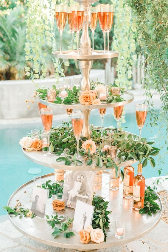 a glam stand with greenery and pastel blooms, candles and drinks for a modern glam wedding