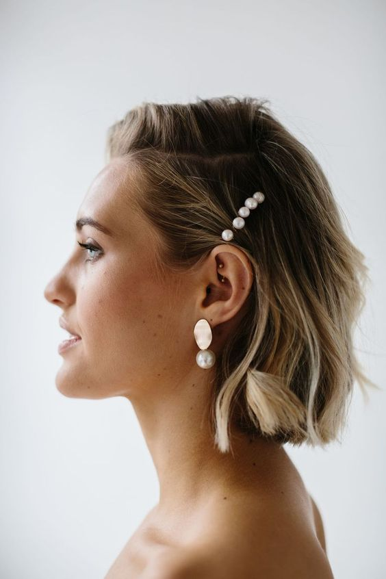 a wavy short bob with some pearl pins and matching gold and pearl earrings for a modern beach bride