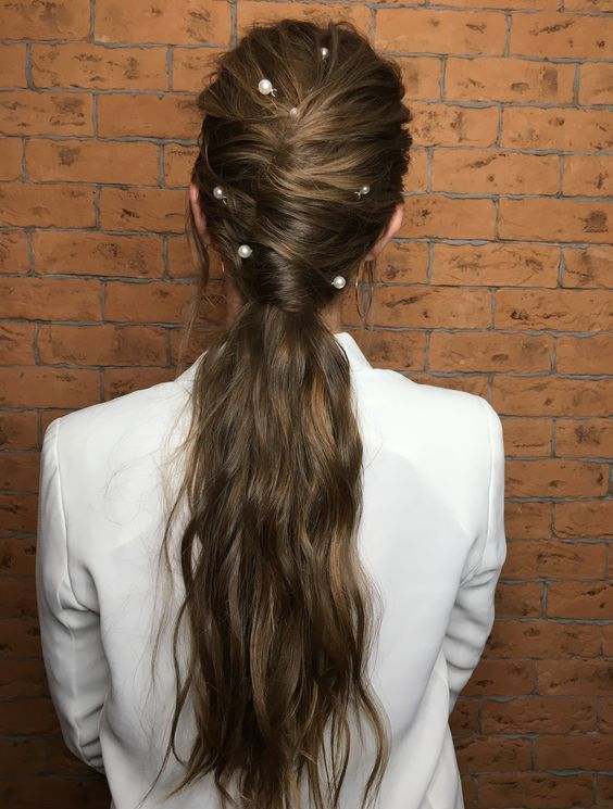 a wavy twisted low ponytail with some locks down and large pearl pins for a bolder accented look