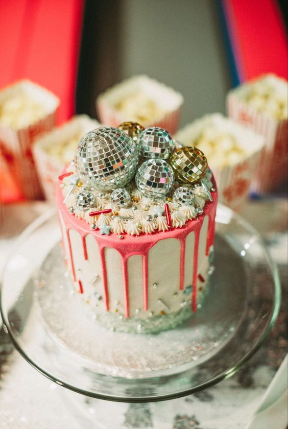 a party-themed wedding cake with pink drip, sparkles, beads and disco balls on top is a very bright idea