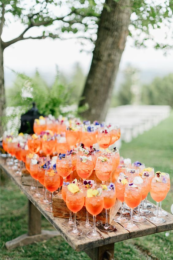 a vintage wooden table with lots of drinks with blooms and wooden stands for drinks