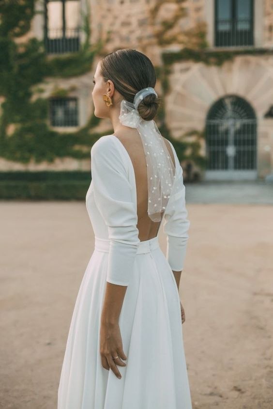 an elegant low bun finished with a sheer veil with pearls is a bold modern and edgy alternative to a usual veil