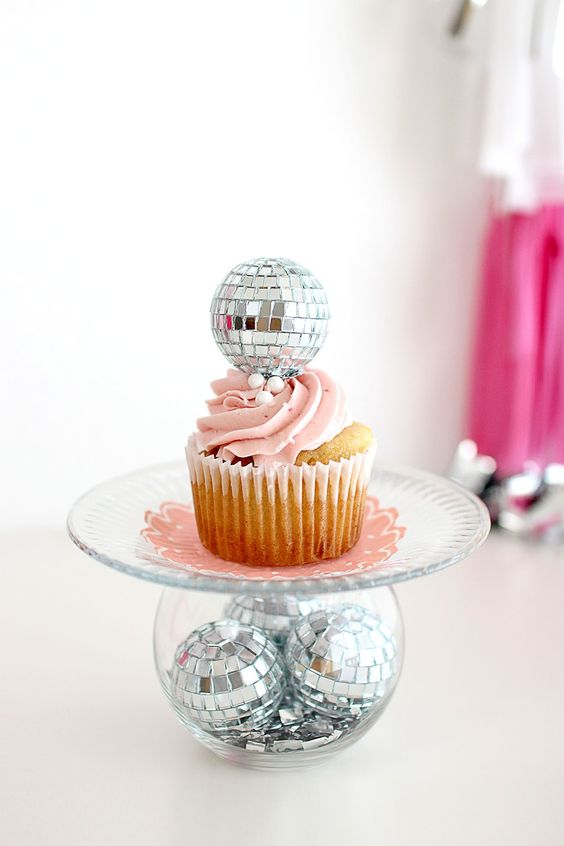 a stand of a bowl with disco balls, a sheer plate and a cupcake topped with a disco ball for a party feel