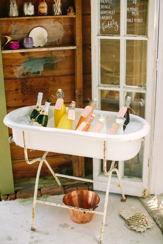a mini tub on a stand with ice and fresh drinks is a simple and cute idea for your wedding