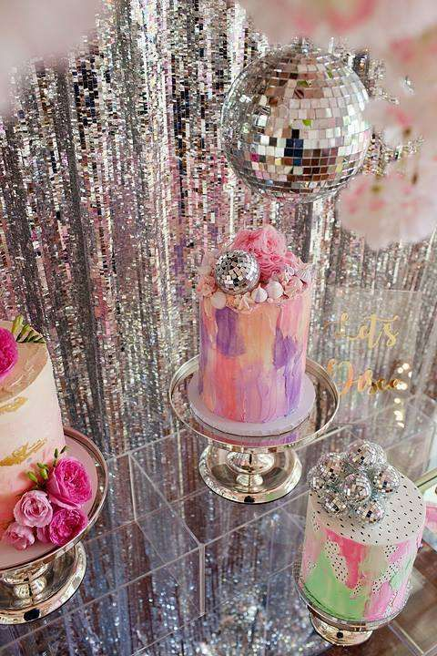 an arrangement of bold painted wedding cakes topped with fresh blooms and disco balls looks super cool