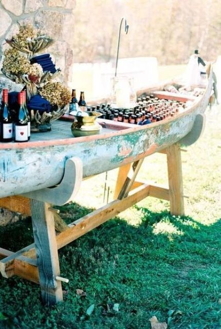 an old boat on a stand, with blooms, bottles, various drinks and napkins is a cool idea for a river wedding