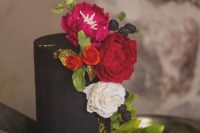 Bride and groom chose a black one tier cake decorated with red, white and pink roses, a greenery and blackberries