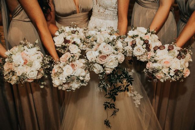Bridesmaids chose bouquets with white and pale pink roses and a greenery