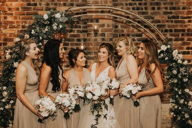 Bridesmaids were dressed in beige V-neck maxi gowns