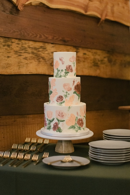 The three tiered wedding cake with floral images was in the same style as all decor details