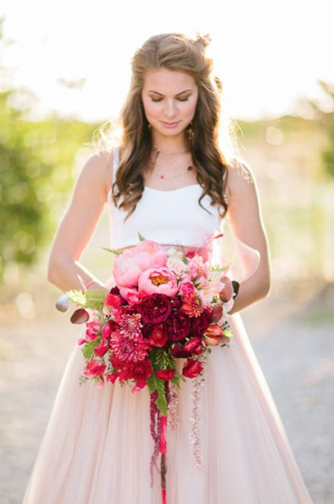 a beautiful ombre wedding bouquet from light pink to hot pink and red and burgundy blooms and greenery makes a statement