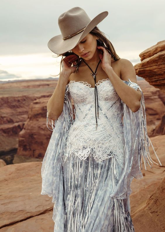 a blue printed corset off the shoulder wedding dress with white lace on the bodice and long fringe plus a hat for a boho feel