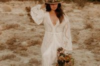 a boho lace A-line wedding dress with a plunging neckline, bell sleeves and long fringe plus a train and a flower detailed hat
