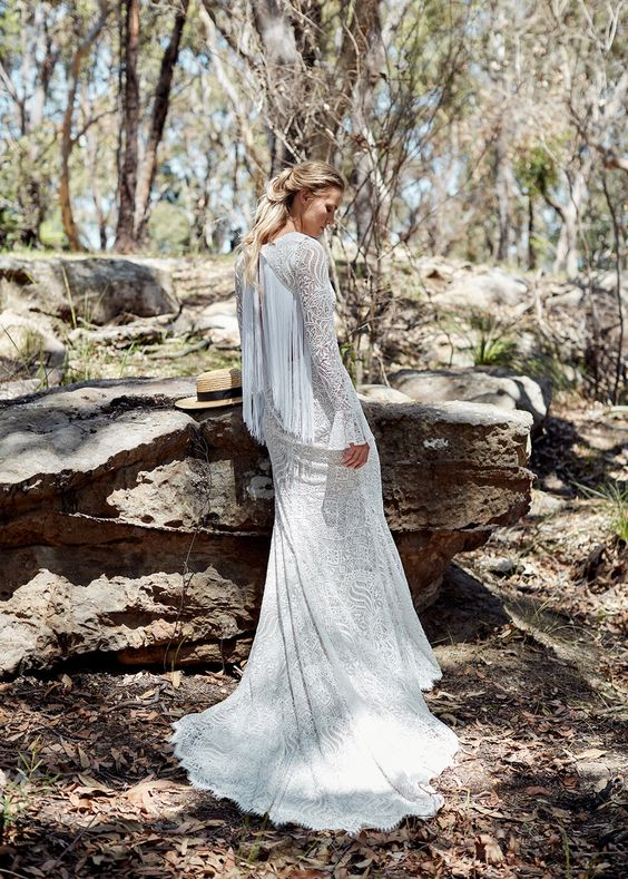 a boho lace A-line wedding gown with long sleeves with a bell touch and a cutout back covered with long fringe for a statement