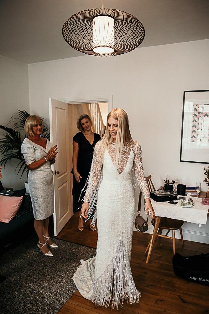 a boho lace embellished sheath wedding dress with an illusion neckline, sleeves and shiny fringe