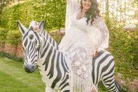 a boho lace embellished wedding dress with a deep V-neckline, long fringe and bell sleeves