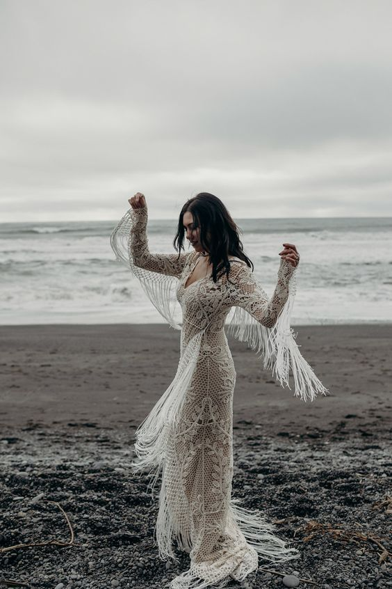 a boho lace sheath wedding dress with long sleeves and long fringe, a V-neckline and a train for a truly boho bride